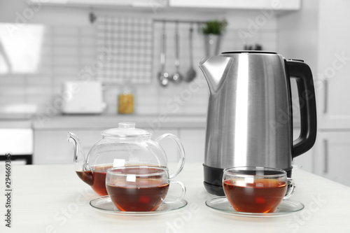 Fotomural  Modern electric kettle, teapot and cups on white wooden table in kitchen