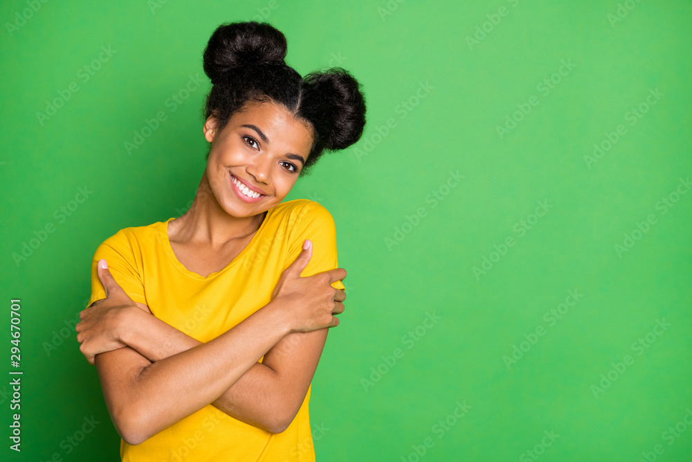 Fototapeta Photo of pretty dark skin lady holding herself in hugs toothy beaming smiling overjoyed wear casual yellow t-shirt isolated green background