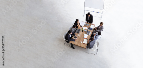 Fototapeta Top view of group of multiethnic busy people working in an office, Aerial view with businessman and businesswoman sitting around a conference table with blank copy space, Business meeting concept obraz na płótnie