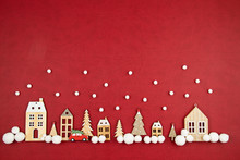 Christmas Composition With Toy  Wooden Houses Over The Red Background