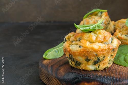 Fotografía homemade cheese muffins with spinach. on dark background.
