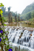 A Waterfall In The Jungle With Waterwheels In The Background