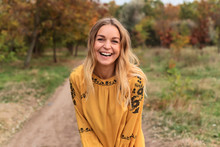 Pretty Woman With Long Blond Hair In Autumn Park