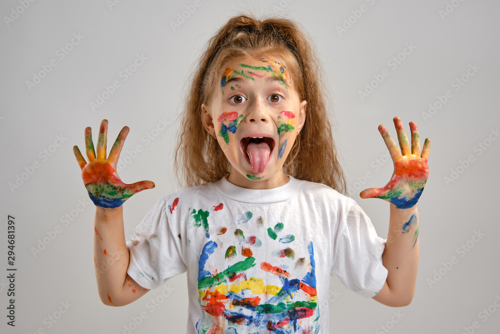 Fototapety, obrazy: Little girl in white t-shirt is posing standing isolated on white and gesticulating with her painted in different colors palms. Art studio. Close-up.