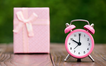 Time To Gift, Shopping Concept, Pink Alarm Clock With A Christmas Gift Box In The Background