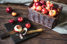 Small Red Apples In A Wicker Box And Peeled Apple And Knife On A Kitchen Board On A Dark Wooden Background.