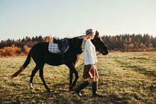 Elegant Woman Walking With Horse In Field