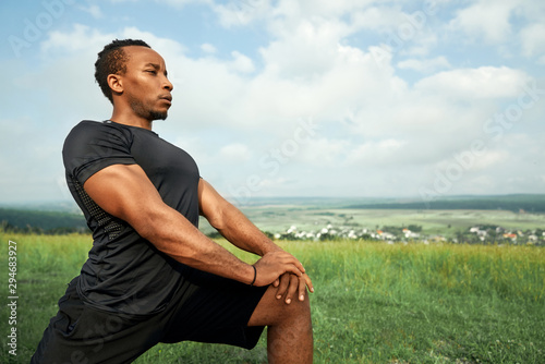 African sportsman doing exercises outdoors. Canvas