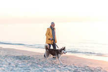 Old Man With Grey Hair And Beard In A Yellow Raincoat With Husky Dog On Leash Walking Along A Beach
