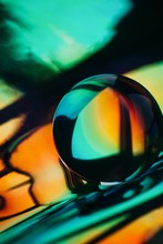Crystal Ball Laying On Holographic Colorful Background
