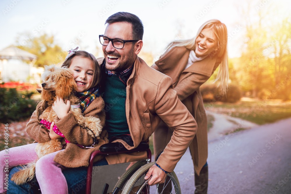 Fototapety, obrazy: Disabled father in wheelchair enjoying with his daughter and wife outdoors in autumn park.
