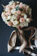 Composition From The Bridal Bouquet Of Beautiful Peonies Flowers With A Pair Of Modish Bridal Shoes On A Dark Blue Background. Concept Of Wedding Preparation. Accessories For A Bride