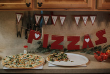 """Pizza On Kitchen Counter With """"""""I Love You To Pizzas' Sign"""