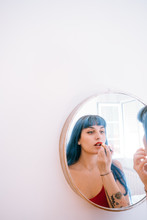 Young Woman With Blue Hair Paints Her Lips In Red In Front Of A Mirror ?