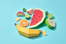 Handcraft Paper Fresh Banana, Slices Of Watermelon, Orange, Lime, Lemon And Mint Leaves On A Blue Background With Space For Text. A Set Of Different Fruits For A Healthy Salad. Flat Lay