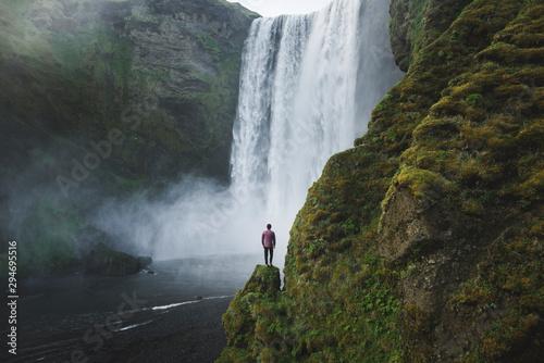 Man standing by Skogafoss waterfall in Iceland - 294695516