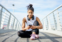 Young Fit Urban Woman Using A Fitness App Whilst Working Out On An Urban Walkway.
