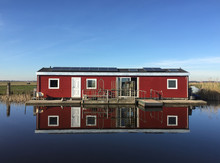 View Of Houseboat Reflected In Lake