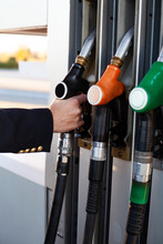 Close-up Of A Men's Hand Using A Fuel Nozzle At A Gas Station