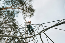 Low Angle View Of Boy On Climb...