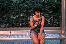 Young Woman With Afro Hair Is Waiting For The Bus At A Stop