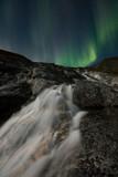 Aurora Borealis over waterfall scene, Greenland