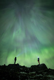 Two people watching the aurora borealis in the night sky
