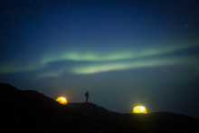 Person By Tents Overlooking Ice Fjord And Icebergs Under Starry Night Sky And Aurora Borealis