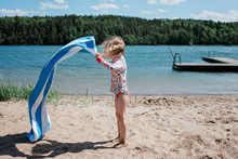Young Girl Shaking Her Towel At The Beach In Sweden