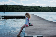 Young Girl Sitting On A Jetty ...