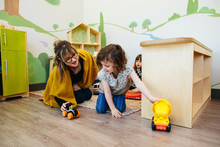 Teacher And Student Interact While Playing With Toy Cars