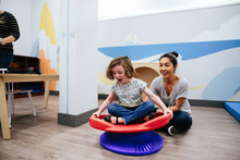 Teacher Smiles While She Spins Her Student On A Sensory Seat