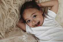 Portrait Of Young Toddler Boy Looking At Camera And Laughing