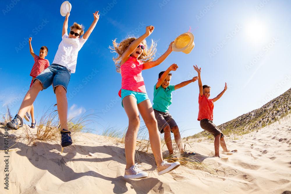 Fototapeta View bellow of many children jump from sand dune