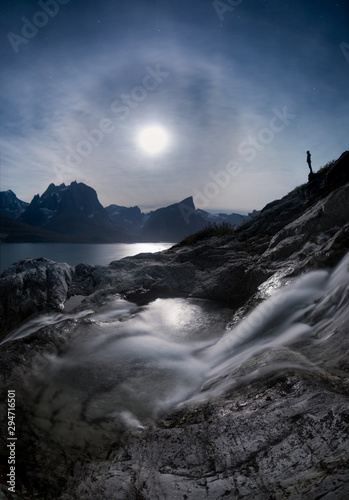 Person standing on rocky shore overlooking lake and mountains at night time next to waterfall - 294716501