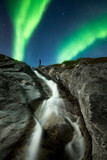 Person standing on above waterfall watching the Aurora Borealis, Greenland