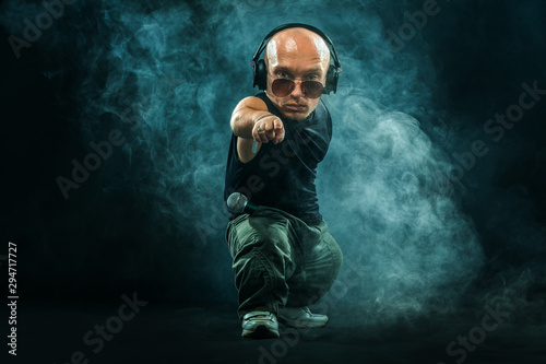 Portrait of stylish midget MC in with headphones and sunglasses posing with microphone Wallpaper Mural