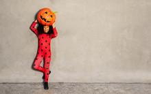 Girl In Ladybug Costume Hold Big Pumpkin Over Wall