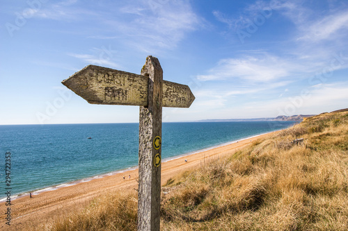 Canvastavla A weather worn wooden sign points the way of the west Dorset coast path along th