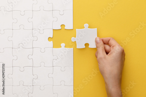 cropped view of woman putting piece of white jigsaw puzzle on yellow background Canvas Print