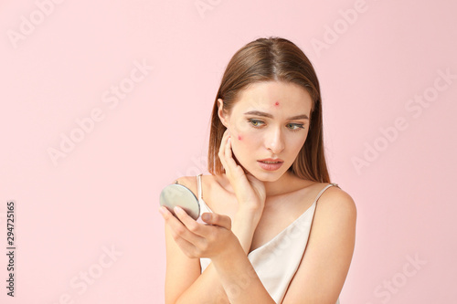 Portrait of young woman with acne problem looking in mirror on color background Wallpaper Mural