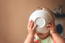 Blond Kid Boy, Very Hungry Eats And Holds A Plate With Both Hands, Close-up With Copyspace