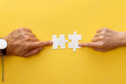 cropped view of woman and man matching pieces of white jigsaw puzzle on yellow b Canvas Print