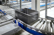 Leinwanddruck Bild - Transportation line conveyor roller with container in motion, selective focus.