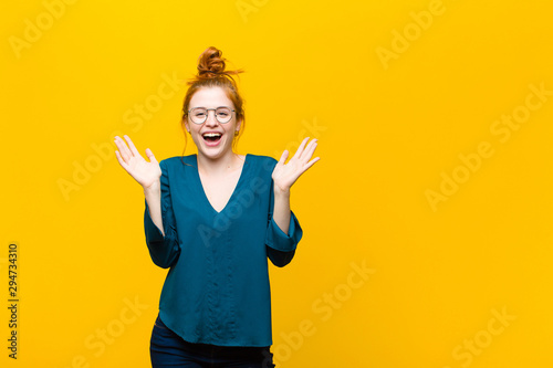 Pinturas sobre lienzo  young red head woman feeling happy, excited, surprised or shocked, smiling and a
