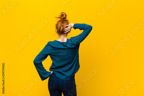 Fotomural young red head woman thinking or doubting, scratching head, feeling puzzled and