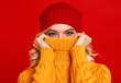 happy emotional cheerful girl laughing  with knitted autumn cap  on colored red background
