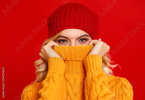 Carta da parati  happy emotional cheerful girl laughing  with knitted autumn cap  on colored red