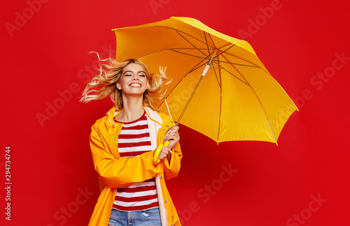 Cadres-photo bureau Ecole de Danse young happy emotional cheerful girl laughing and jumping with yellow umbrella on colored red background.