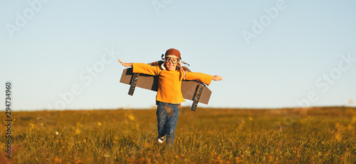 Child pilot aviator with wings of airplane dreams of traveling in summer  at sunset. - 294734960